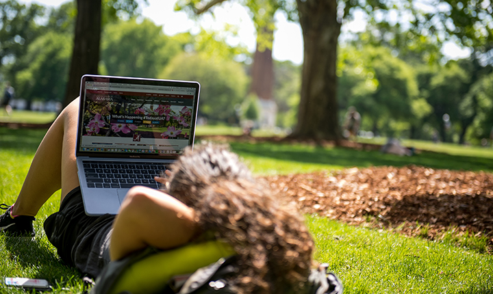 Student using laptop on the Quad